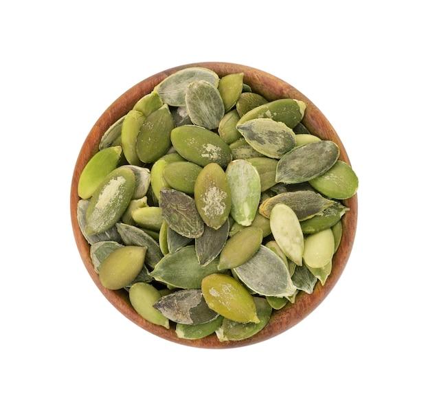 Nasiona dyni w drewnianej misce, na białym tle. nasiona zielonej pepity. widok z góry.