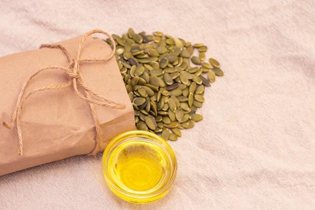 Nasiona dyni w papierowej torebce, olej z pestek dyni na naturalnym lnie. nasiona dyni witaminy z grupy b i magnezu.
