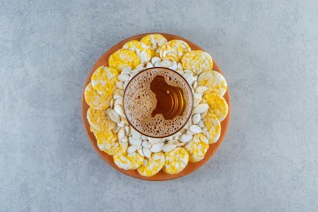 Nasiona, frytki i pół litra na talerzu, na marmurowej powierzchni.