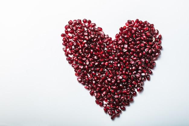 Nasiona granatu w kształcie serca na białym tle.