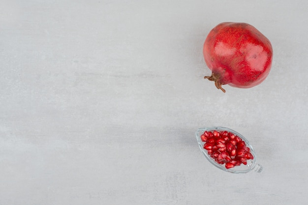 Nasiona granatu w szkle i granatu na białym tle.