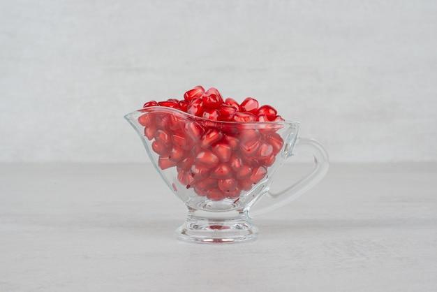 Nasiona granatu w szkle na białym stole