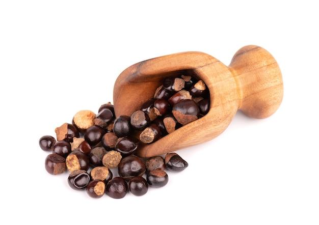 Nasiona guarany w drewnianej miarce, na białym tle na białej powierzchni