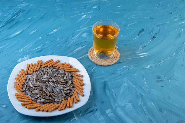 Nasiona i grzanki na talerzu obok kufla piwa, na niebieskim tle.