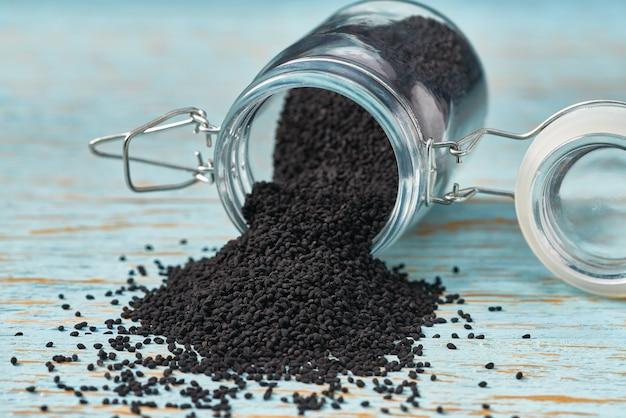 Nasiona kminku czarnego wylewa się ze szklanego słoika na niebieskim drewnianym stole