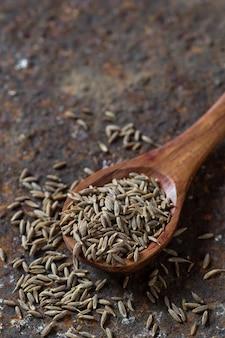 Nasiona kminku w drewnianą łyżką na teksturowanej powierzchni