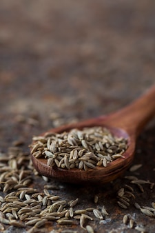 Nasiona kminku w drewnianą łyżką na tle z teksturą