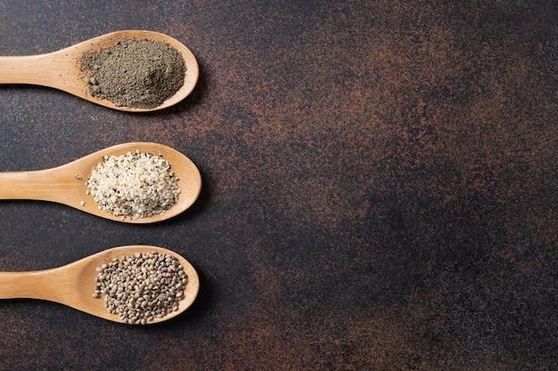 Nasiona konopi, mąka, ziarna w łyżkach na ciemnym tle. widok z góry.