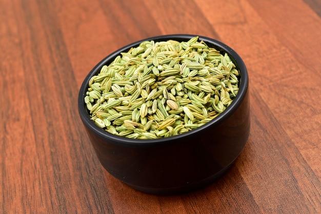 Nasiona kopru włoskiego w misce blacl na drewnianym stole.