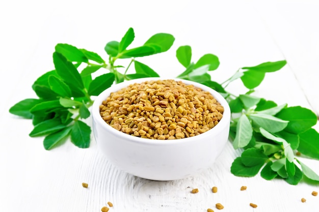 Nasiona kozieradki w misce i na stole, przyprawy zielone liście na tle deska