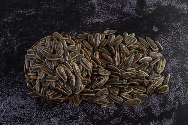 Nasiona kwiatów słonecznych w drewnianej misce na podłodze z czarnego cementu.