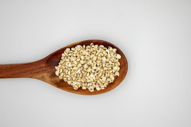 Nasiona łez hioba lub proso w drewnianej łyżce