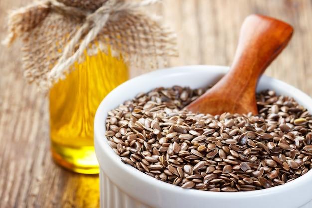 Nasiona lnu i olej w butelce na drewnianym tle