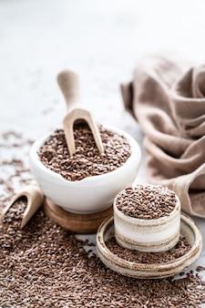 Nasiona lnu w ceramicznej misce drewnianą łyżką. zdrowa żywność ekologiczna. zdjęcie pionowe