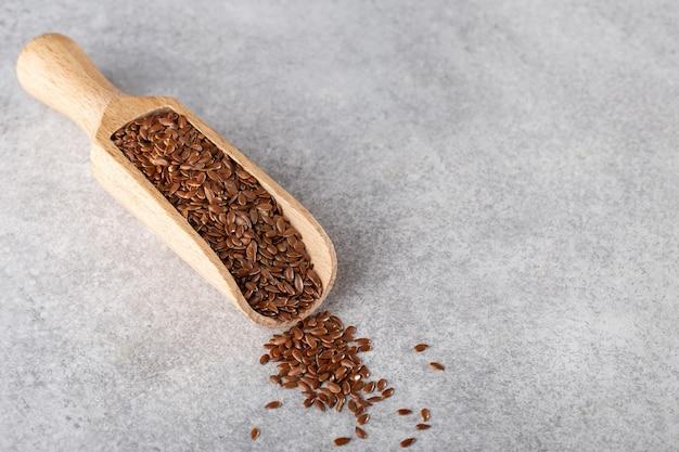 Nasiona lnu w drewnianej łyżce do produktów sypkich