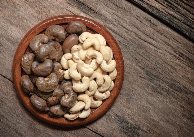 Nasiona orzechów nerkowca są ułożone w yin i yang na starym drewnianym stole. widok z góry, płasko ułożone.