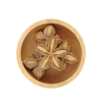 Nasiona orzeszków ziemnych sacha inchi w drewnianej misce na białym tle. widok z góry