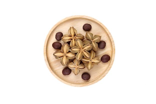Nasiona orzeszków ziemnych sacha inchi w drewnianej płycie na białym tle. widok z góry