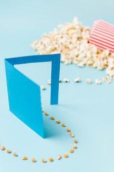 Nasiona popcornu wchodzą przez drzwi papierowe zamieniając się w popcorn na niebieskim tle