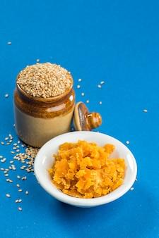Nasiona sezamu w glinianym garnku z jaggery w misce na niebieskiej powierzchni