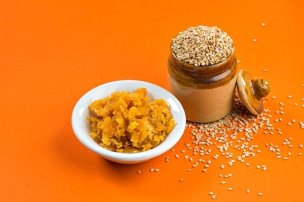 Nasiona sezamu w glinianym garnku z jaggery w misce