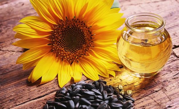 Nasiona słonecznika i butelka oleju na stare drewniane tła. selektywne skupienie.natura