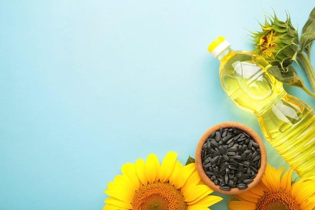 Nasiona słonecznika i butelkę oleju na niebieskim tle. widok z góry