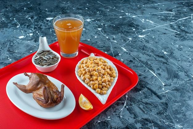 Nasiona słonecznika pokrojone w plasterki cytryny, grillowany kurczak i szklanka piwa na tacy, na marmurowym stole.
