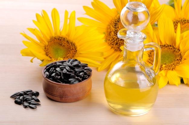 Nasiona słonecznika w drewnianej misce i olej słonecznikowy oraz kilka pięknych żółtych słoneczników na naturalnym drewnianym tle