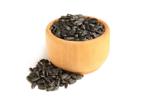 Nasiona słonecznika w drewnianej misce na białym tle.
