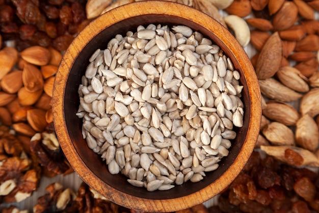 Nasiona słonecznika w drewnianej płycie cedrowej w tle rozproszenie różnych orzechów.