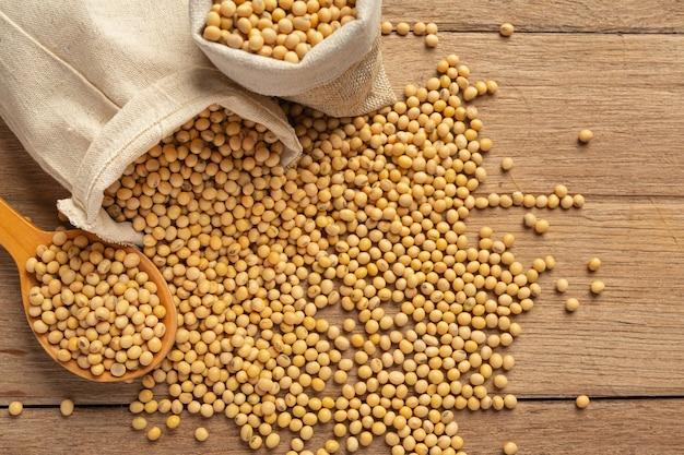 Nasiona soi na drewnianej podłodze i workach konopnych pojęcie odżywiania żywności.