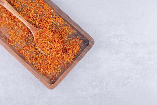 Nasiona szafranu na drewnianym talerzu na betonowym tle. zdjęcie wysokiej jakości