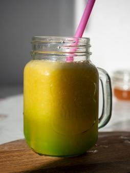 Nasłoneczniony szklany słoik z żółtymi koktajlami. w słoiku jest rurka do picia. drewniane tło. zdjęcie pionowe