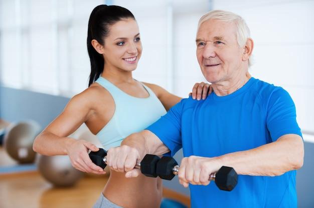 Następny krok do pełnego wyzdrowienia. pewna siebie fizjoterapeutka pomaga starszemu mężczyźnie w fitness w klubie fitness