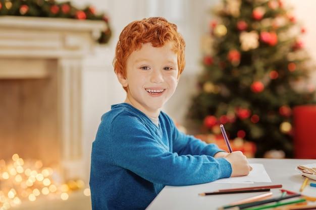 Następny wielki artysta. ujęcie w górę pozytywnie nastawionego małego chłopca, który odwraca głowę i uśmiecha się, pracując w domu nad nowym kolorowym arcydziełem.