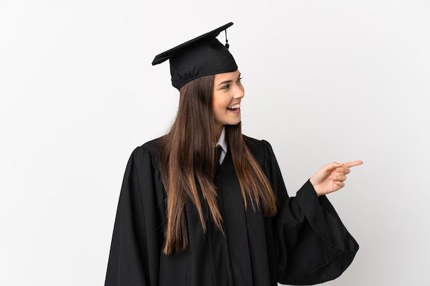 Nastolatek absolwent uniwersytetu brazylijskiego na białym tle, wskazując palcem w bok i prezentując produkt