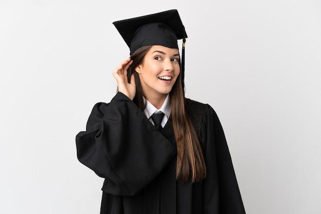Nastolatek absolwent uniwersytetu brazylijskiego na pojedyncze białe tło słuchając czegoś, kładąc rękę na uchu
