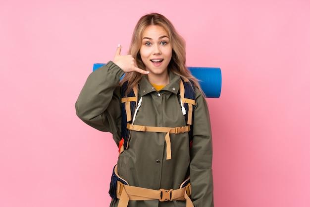 Nastolatek alpinista dziewczyna z dużym plecakiem na różowej ścianie robi telefonicznemu gestowi