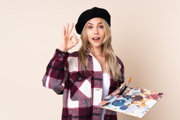 Nastolatek artysty dziewczyna trzyma paletę na błękit ścianie zaskakującej i pokazuje ok znaka