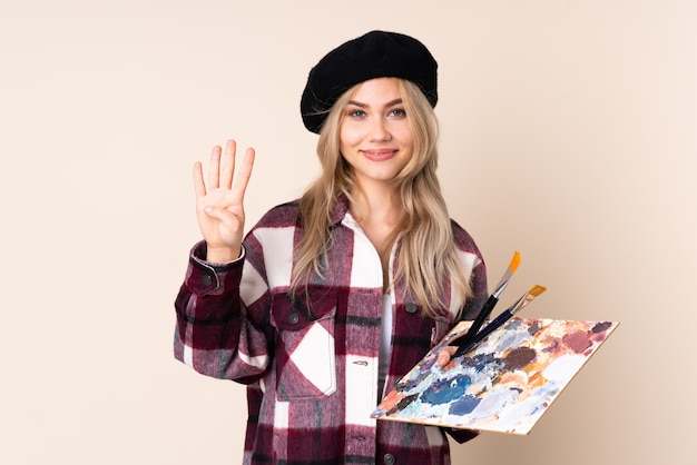 Nastolatek artysty dziewczyna trzyma paletę na niebieską ścianę szczęśliwy i licząc cztery z palcami