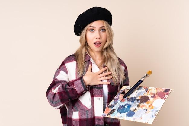 Nastolatek artysty dziewczyna trzyma paletę odizolowywająca na błękit ścianie zaskakuje i szokuje podczas gdy patrzejący dobrze