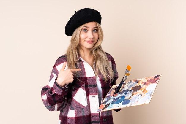Nastolatek artysty kobieta trzyma paletę odizolowywająca na błękit ścianie wskazuje on