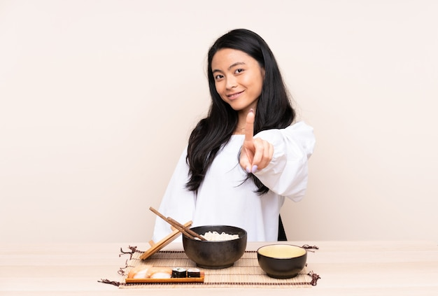 Nastolatek azjatycka dziewczyna je azjatykciego jedzenie na beż ścianie pokazuje i podnosi palec