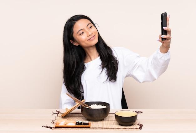 Nastolatek azjatycka dziewczyna je azjatykciego jedzenie na beż ścianie robi selfie
