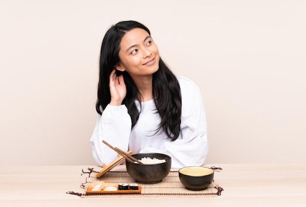 Nastolatek azjatycka dziewczyna je azjatykciego jedzenie odizolowywającego na beżu