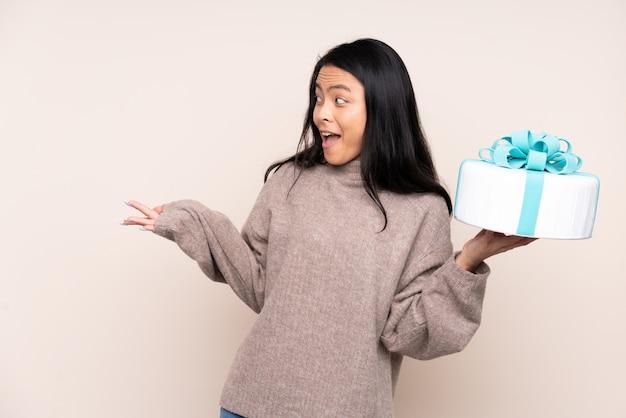Nastolatek azjatycka dziewczyna trzyma dużego tort na beż ścianie z zdziwionym wyrazem twarzy