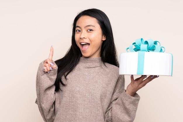 Nastolatek azjatycka dziewczyna trzyma dużego tort na beżowej ścianie wskazuje w górę doskonałego pomysłu