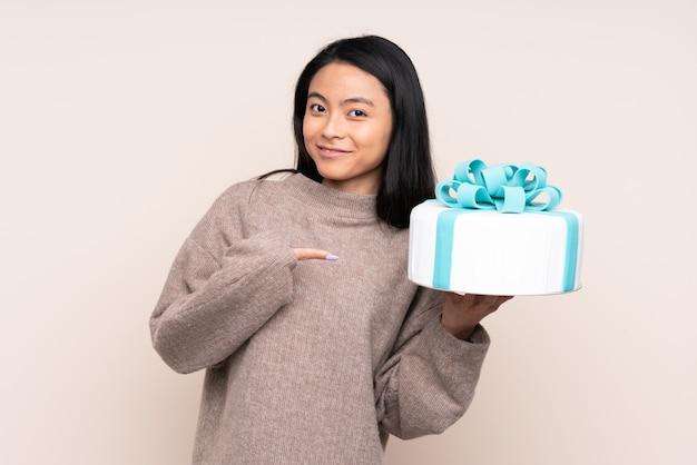 Nastolatek azjatycka dziewczyna trzyma dużego tort na beżowej ścianie z niespodzianka wyrazem twarzy