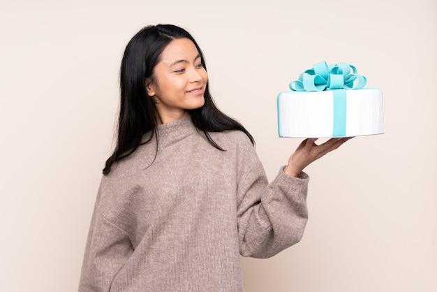 Nastolatek azjatycka dziewczyna trzyma dużego tort odizolowywający na beż ścianie z szczęśliwym wyrażeniem